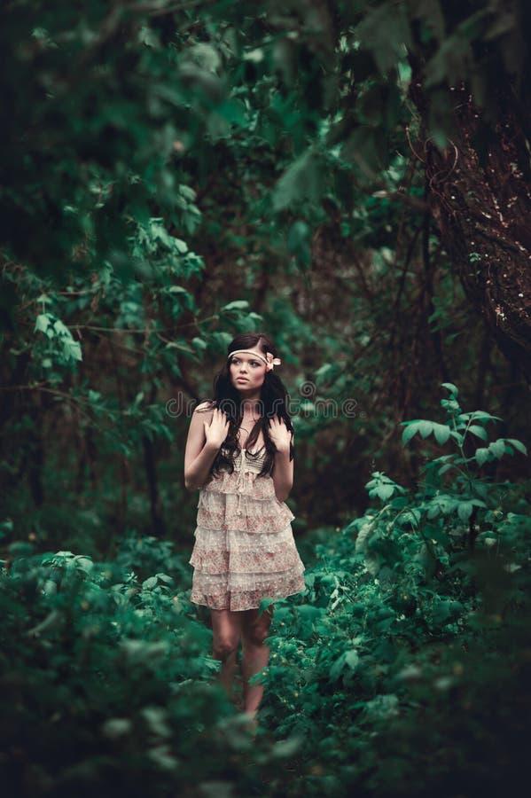 Brunettemädchen im kurzen Kleid im Wald lizenzfreie stockbilder