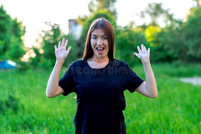 Brunettemädchen im Sommerpark draußen In einem schwarzen T-Shirt Handgestenlächeln glücklich Gefühle der Überraschung klammern lizenzfreie stockfotos