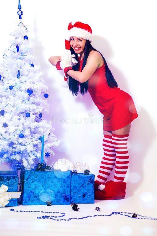 Brunettemädchen mit dem langen Haar in einer roten Gnomklage und einer gestreiften Kappe an einem Baum der weißen Weihnacht verzi lizenzfreies stockbild