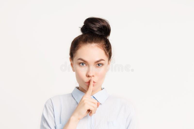 Brunettemädchen mit dem langen Haar hält Finger nahe Lippen die Geste der Ruhe, Geheimnis, Geheimnis lizenzfreies stockfoto