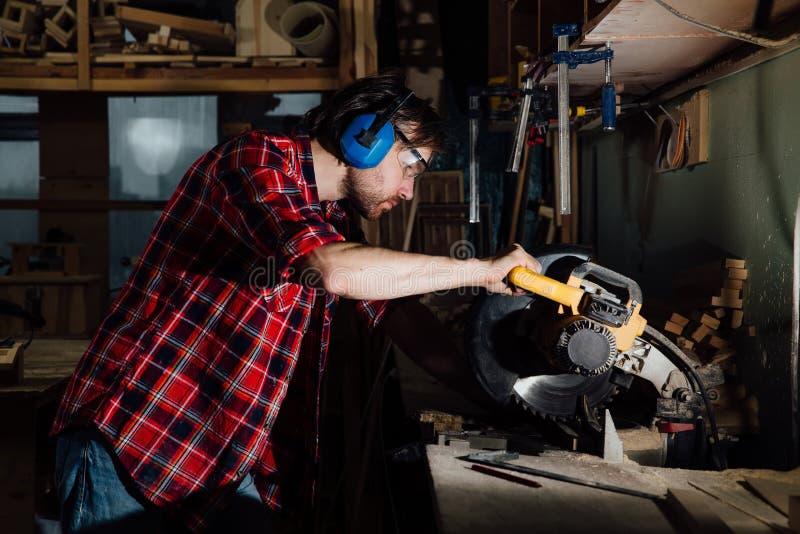 Brunettemannberuftischler-Erbauersägen mit Kreissäge ein hölzernes Brett lizenzfreie stockfotografie