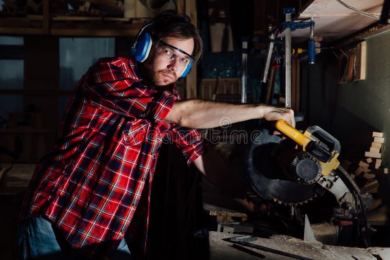 Brunettemannberuftischler-Erbauersägen mit Kreissäge ein hölzernes Brett lizenzfreies stockbild
