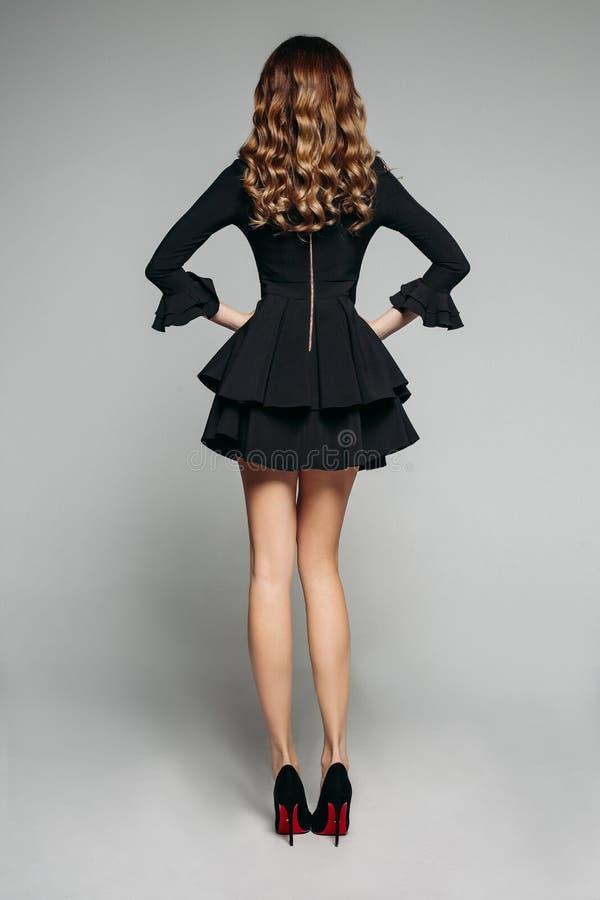 Brunettemodell mit dem gewellten Haar, das im schönen schwarzen Kleid mit flounced Rock und hohen Absätzen aufwirft stockfotografie