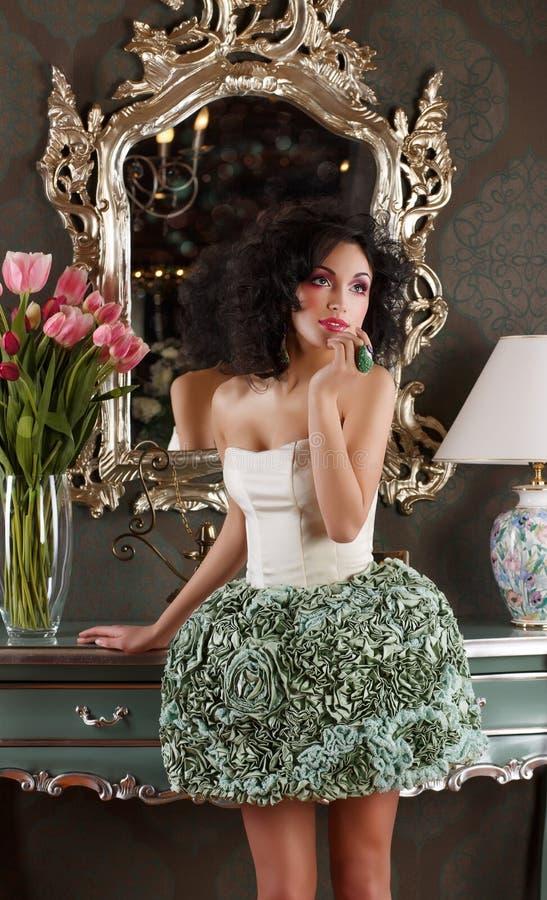 Coquette. Den lockiga hårkvinnan i elegant klänning över tappning avspeglar fotografering för bildbyråer