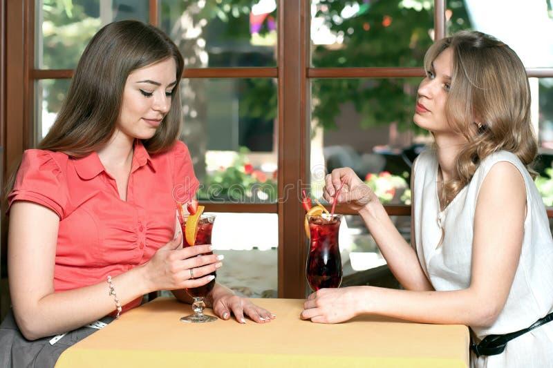 Brunetten och blondinen dricker sammanträde för fruktdrink i kafé royaltyfria foton