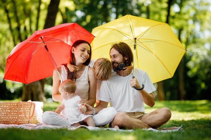 Brunetter som föräldrar med två ungar har, vilar på gräsmattan under de ljusa röda och gula paraplyerna som täcker dem från royaltyfri foto