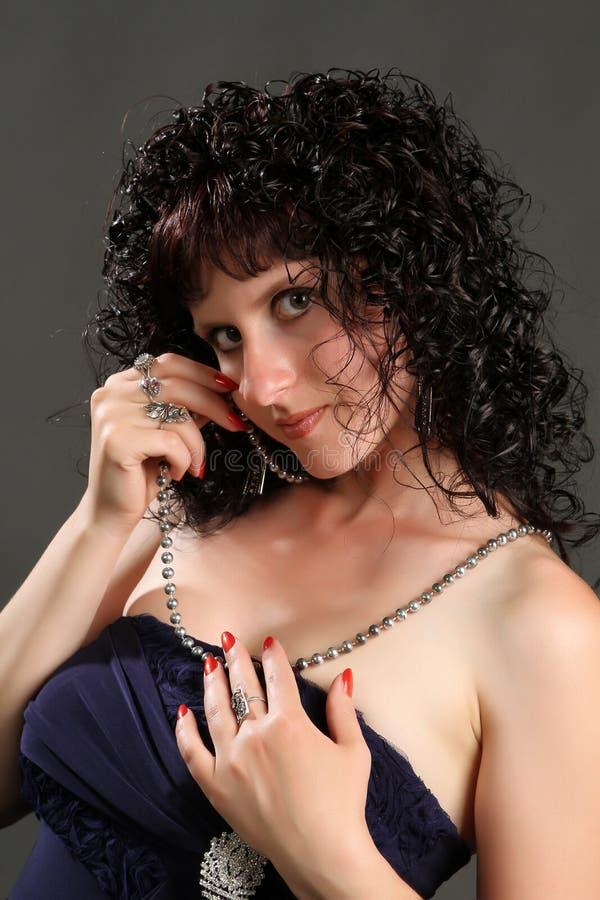 Brunetteschwarzkleid auf einem dunklen Hintergrund stockfoto