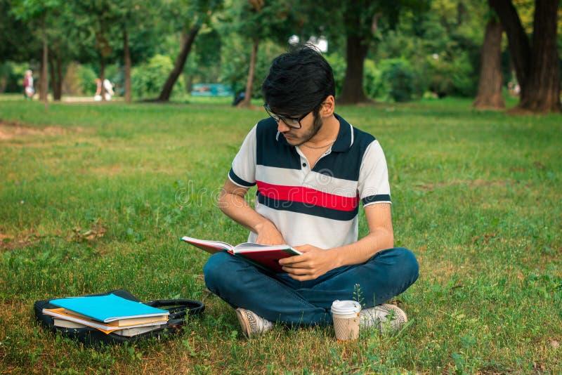 Brunettestudentenmann-Lesebücher auf einem Gras lizenzfreie stockfotos