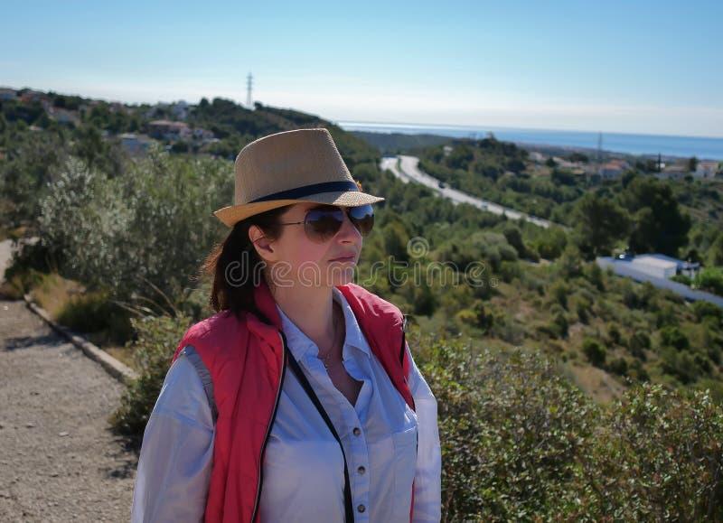 Brunettflicka i en hatt och solglasögonblickar på vägen bort royaltyfri fotografi