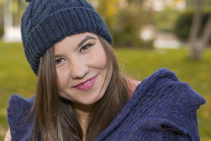 Brunettflicka i en stucken hatt i en parkera i höst royaltyfri foto
