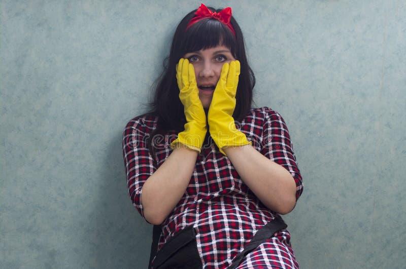 Brunettflicka i gula handskar med öppen munbrunett arkivbilder