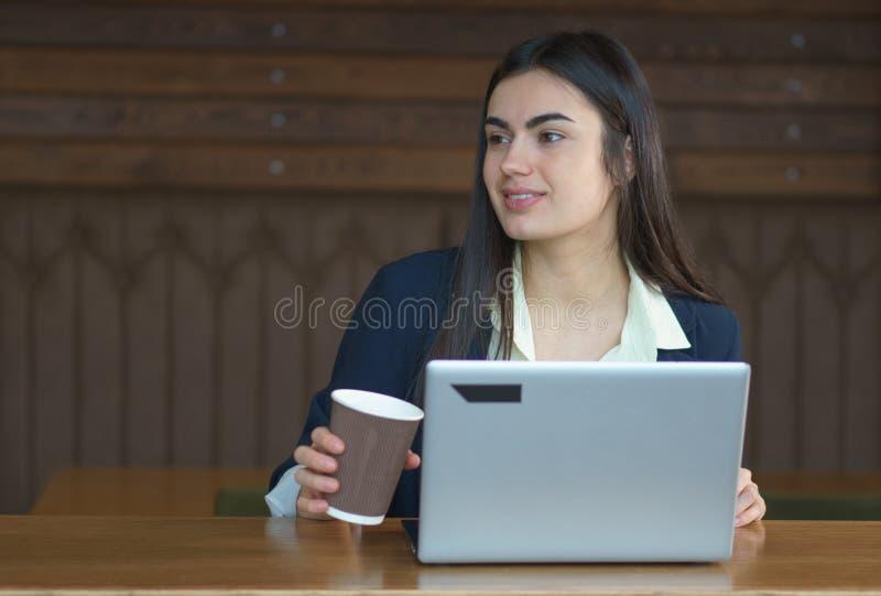 Brunettflicka med en bärbar dator och ett kaffe som arbetar i kafé i kaffeavbrott arkivfoton