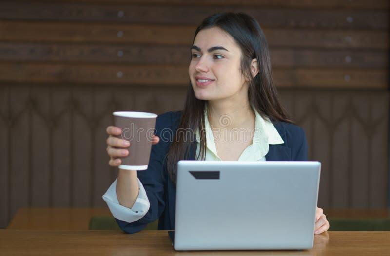 Brunettflicka med en bärbar dator och ett kaffe som arbetar i kafé i kaffeavbrott fotografering för bildbyråer