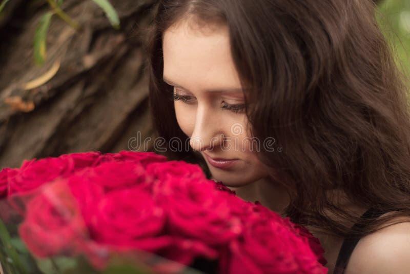 Brunettflicka med en bukett av röda rosor royaltyfri fotografi