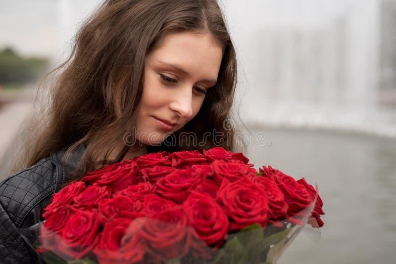 Brunettflicka med en bukett av röda rosor royaltyfria foton