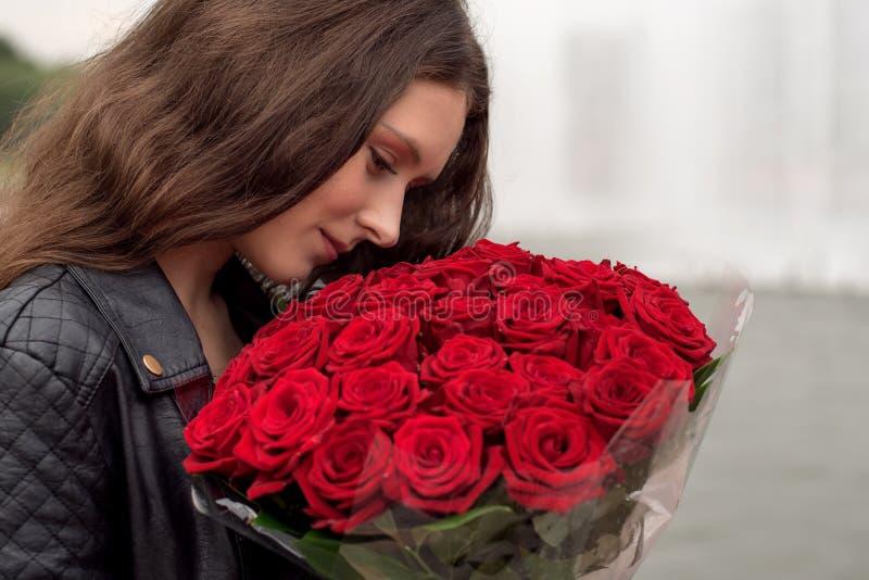 Brunettflicka med en bukett av röda rosor fotografering för bildbyråer