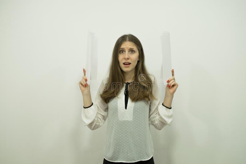 Brunettflicka med flödande hårställningar i mitten av ramen som rymmer vita ark i hennes händer fotografering för bildbyråer