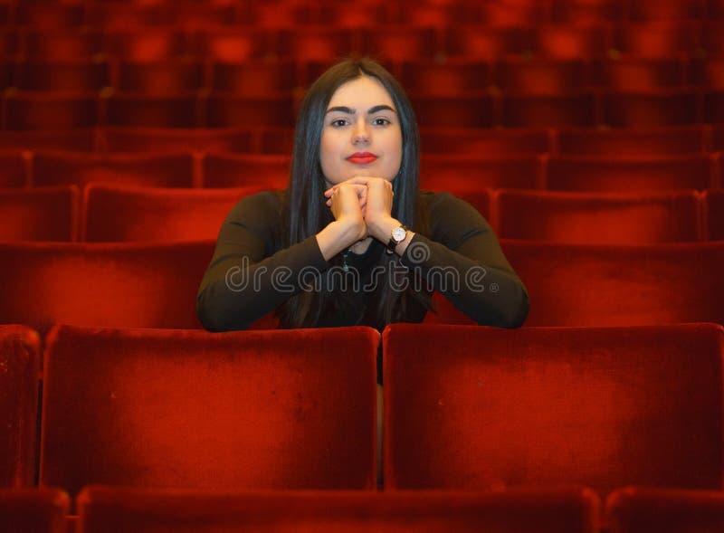 Brunettflicka med händer under henne framsidasammanträde i den tomma röda teaterkorridoren arkivfoto