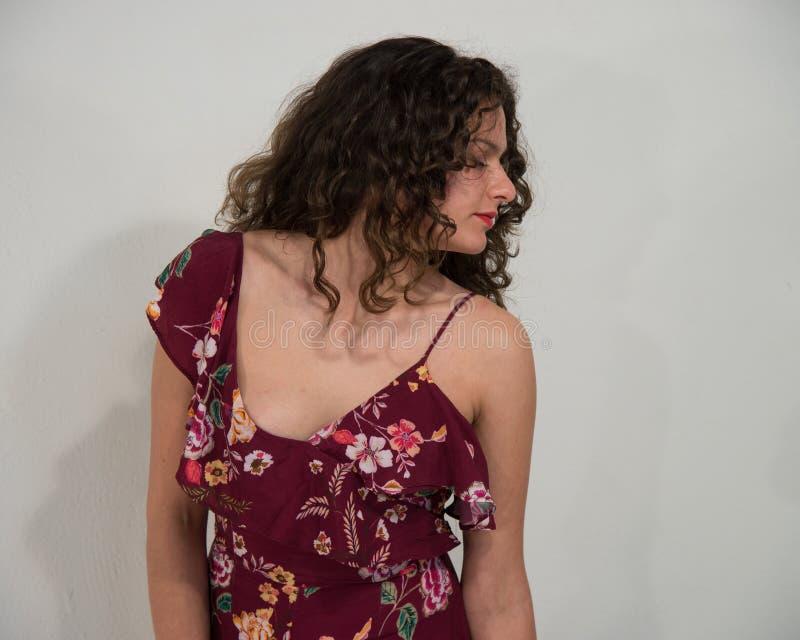 Brunettflicka med långt lockigt hår, med klänningen med tunna remmar, arkivfoto