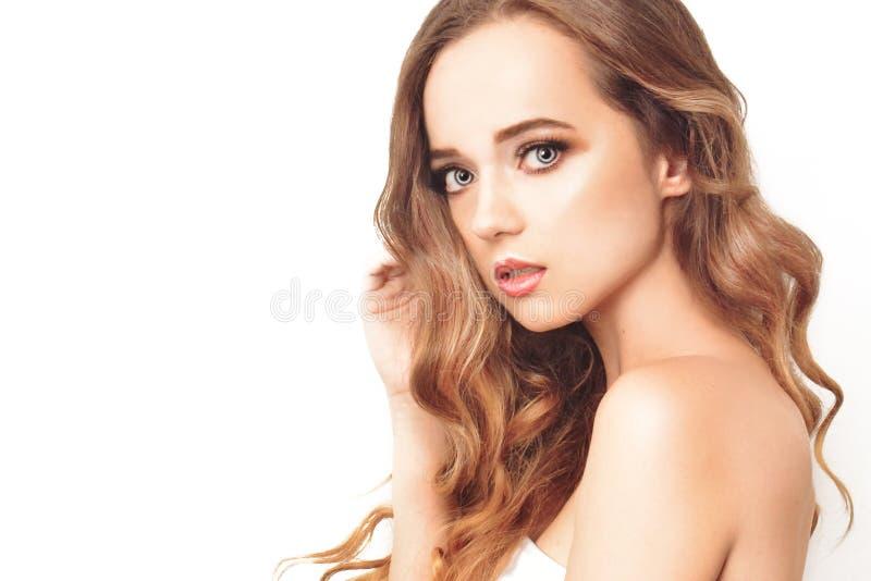 Brunettflicka med långt och skinande långt hår Härlig modellkvinna med lockig frisyr- och innegrejmakeup royaltyfria bilder