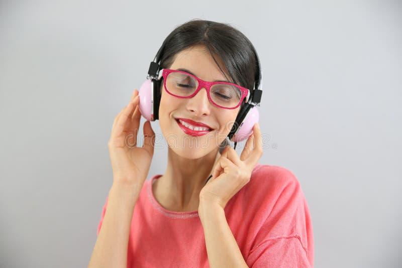 Brunettflicka med lyssnande musik för glasögon royaltyfri fotografi