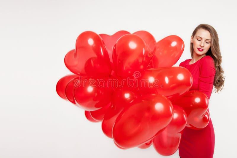 Brunettflicka som rymmer röda bollar i form av hjärtor på en vit bakgrund för dag för valentin` s arkivfoto