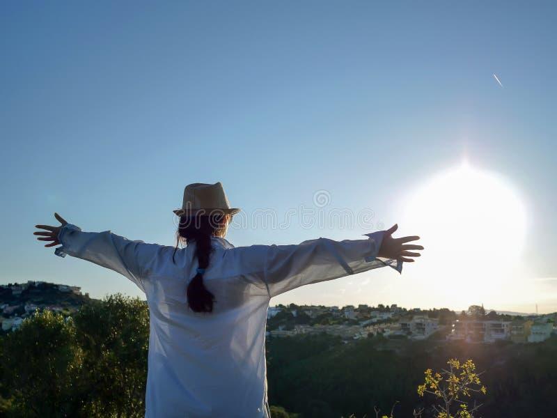 Brunettflickan i en hatt och en blå skjorta möter soluppgången med lyftta armar, copyspace arkivfoton
