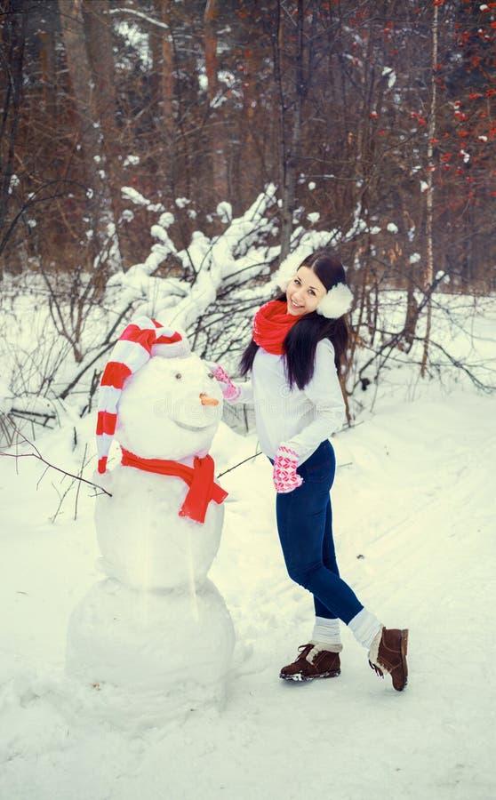 Brunettflickan i hatt och tumvanten hugger en snögubbe arkivbilder