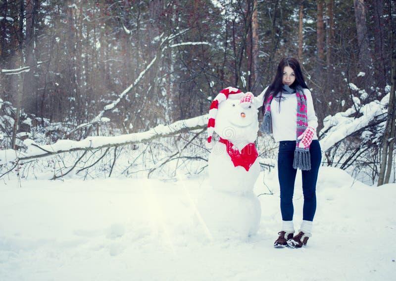 Brunettflickan i hatt och tumvanten hugger en snögubbe fotografering för bildbyråer