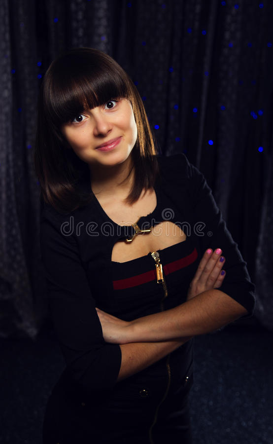 Brunettflickan i svart klänning på en bakgrund av snör åt och bokeh fotografering för bildbyråer