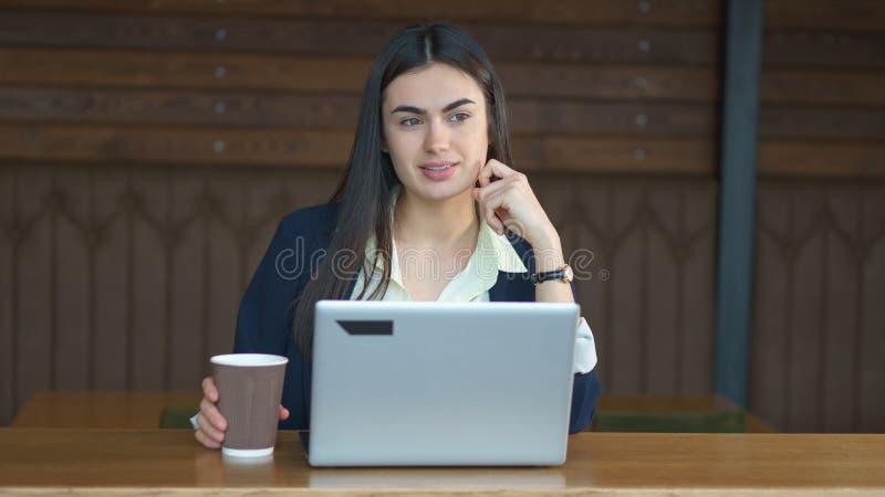 Brunettflickan med en bärbar dator och ett kaffe tänker, innan han gör ett viktigt beslut royaltyfri foto