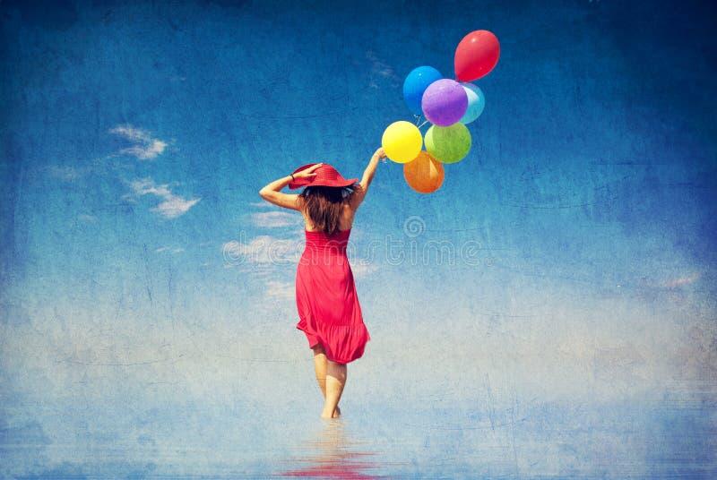 Brunettflickan med färgar ballonger på seglar utmed kusten. royaltyfri bild
