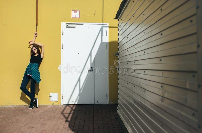 Brunettflickan vaggar in svart stil som utomhus står mot den gula väggen i stadsgatan royaltyfria bilder