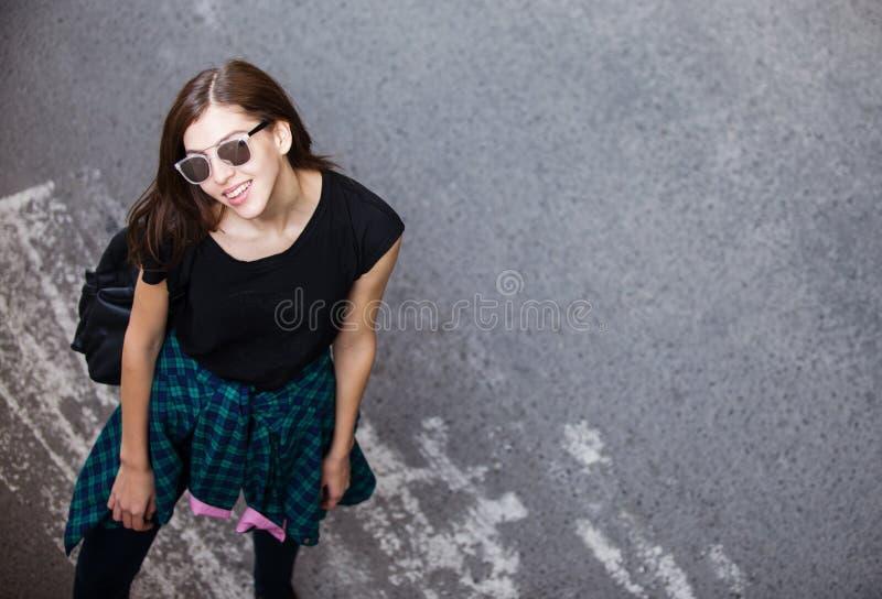 Brunettflickan vaggar in svart stil, stående det fria i stadsgatan fotografering för bildbyråer