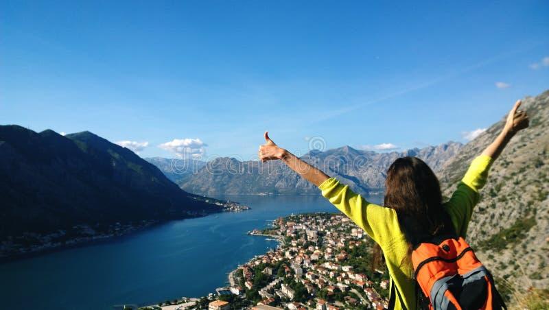 Brunettflickaställningar överst av ett berg och att se i riktningen av den Boko-Kotor fjärden till Kotor i Montenegro handelsresa arkivbilder