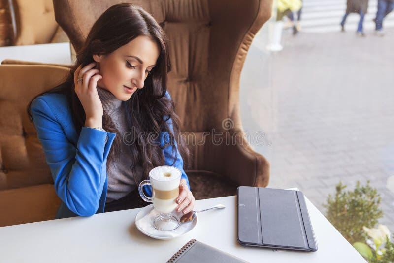 Brunettkvinna i affärskläder: grå tröja och blått omslag arkivfoton