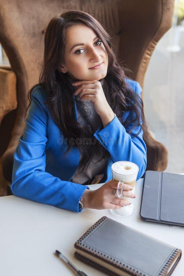 Brunettkvinna i affärskläder: grå tröja och blått omslag royaltyfria foton