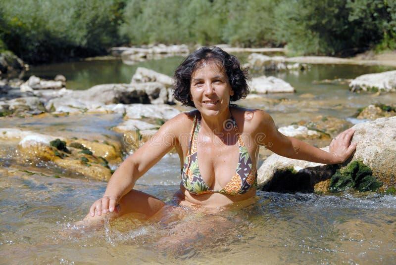 Brunettkvinna i en baddräkt, bad i floden royaltyfri foto