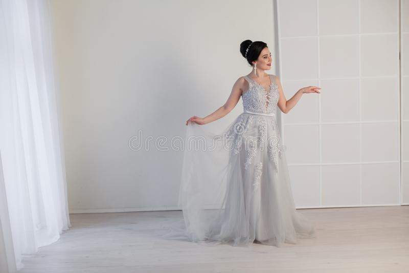 Brunettkvinna i grå bröllopkappa royaltyfri fotografi