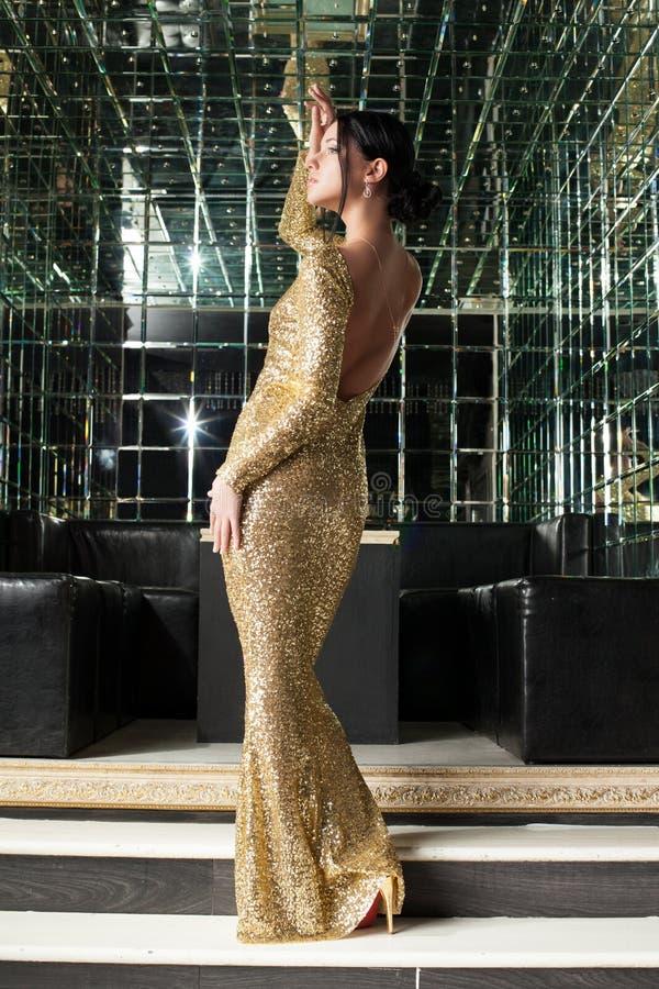 Brunettkvinna i guld- klänning royaltyfri bild