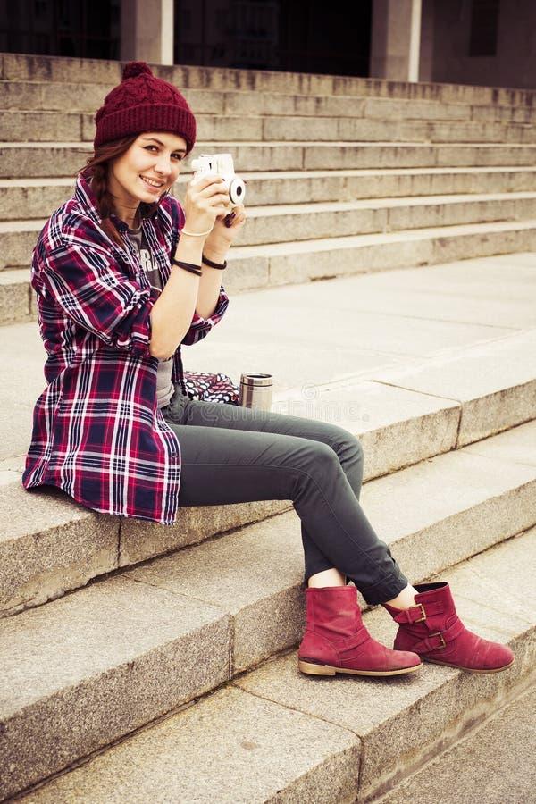 Brunettkvinna, i hipsterdräktsammanträde på moment och att fotografera på retro kamera på gatan tonad bild royaltyfri fotografi