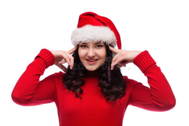 Brunettkvinna i julhattbruk dina fingrar att peka till huvudet på vit bakgrund royaltyfria foton