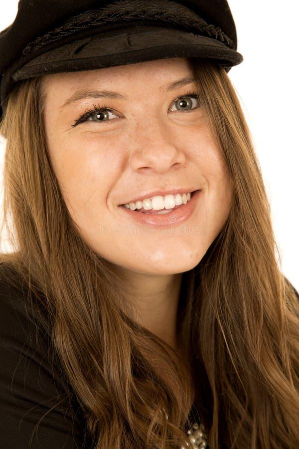 Brunettkvinna med gröna ögon som bär le för svart hatt royaltyfria bilder