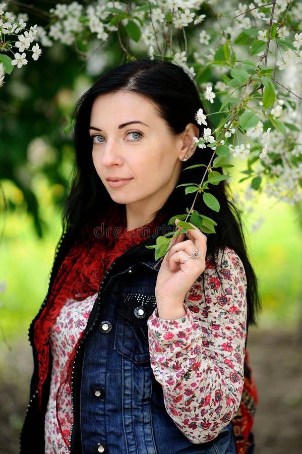 Brunettkvinna med långt hår under körsbärsrött träd i blomning arkivfoto