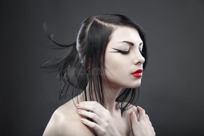 Brunettkvinna med långt rakt hår på mörker royaltyfria bilder