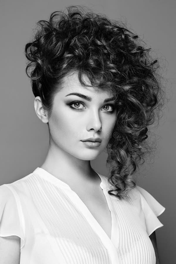 Brunettkvinna med lockigt och skinande hår arkivfoto