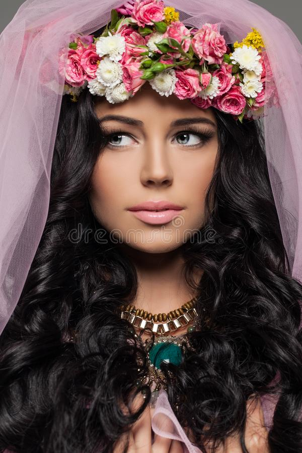 Brunettkvinna med makeup och blommafrisyren royaltyfri foto