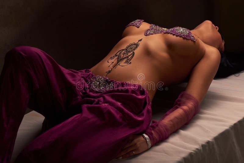 Brunettkvinna med mehendi på hennes mage arkivbilder