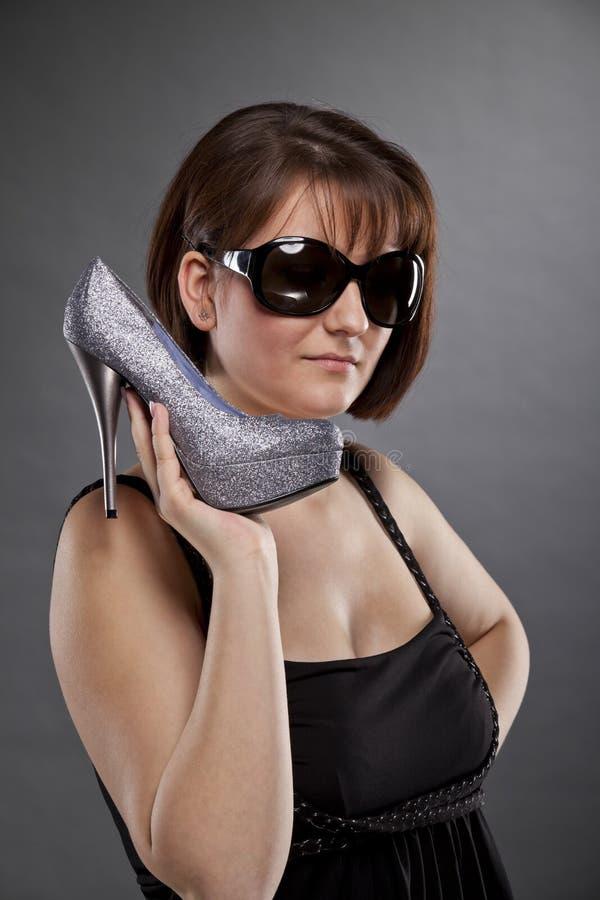 Brunettkvinna med solglasögon som rymmer en sko royaltyfri fotografi