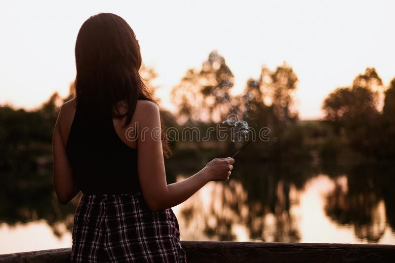 Brunettkvinna p? solnedg?ngen p? en sj? med en r?kelsepinne fotografering för bildbyråer